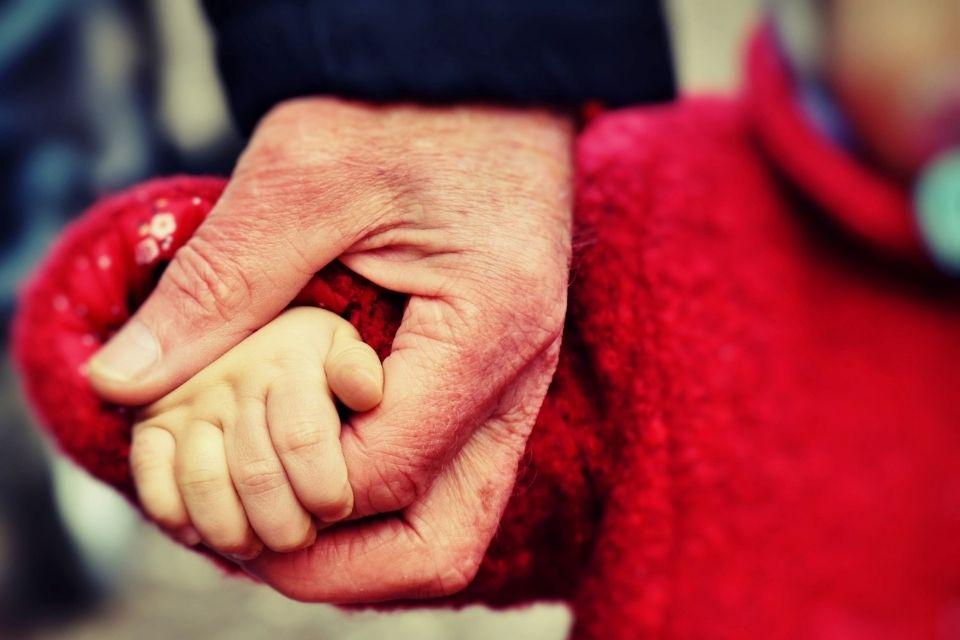 oude hand houdt jong kind hand vast