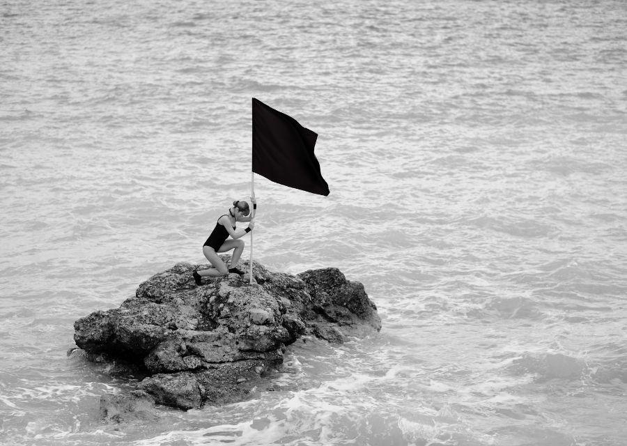 vrouw op stuk land in zee geknield met vlag